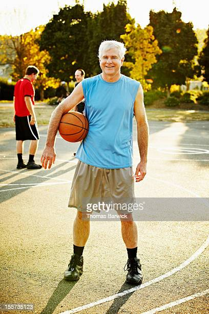Smiling mature basketball player standing on court