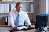 Smiling mature businessman at office desk with a computer