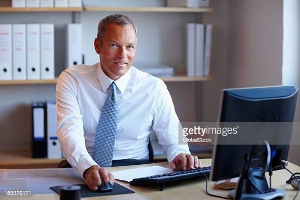 Lächelnd Reifer Geschäftsmann am Schreibtisch mit computer