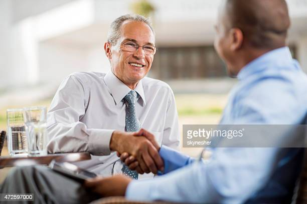 Smiling mature businessman shaking hands with his colleague.