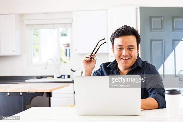 Smiling mature businessman typing on laptop in kitchen