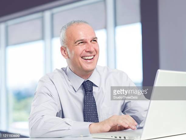 Lächelnd Reifer Geschäftsmann mit laptop