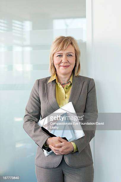 Smiling mature businesswoman holding folder
