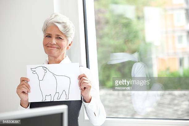 Smiling mature businesswoman holding paper with bull figure