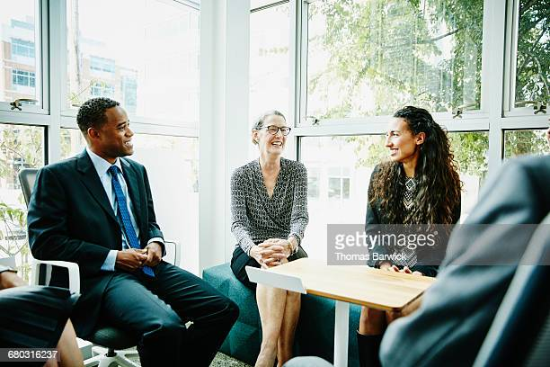 Smiling mature businesswoman leading team meeting