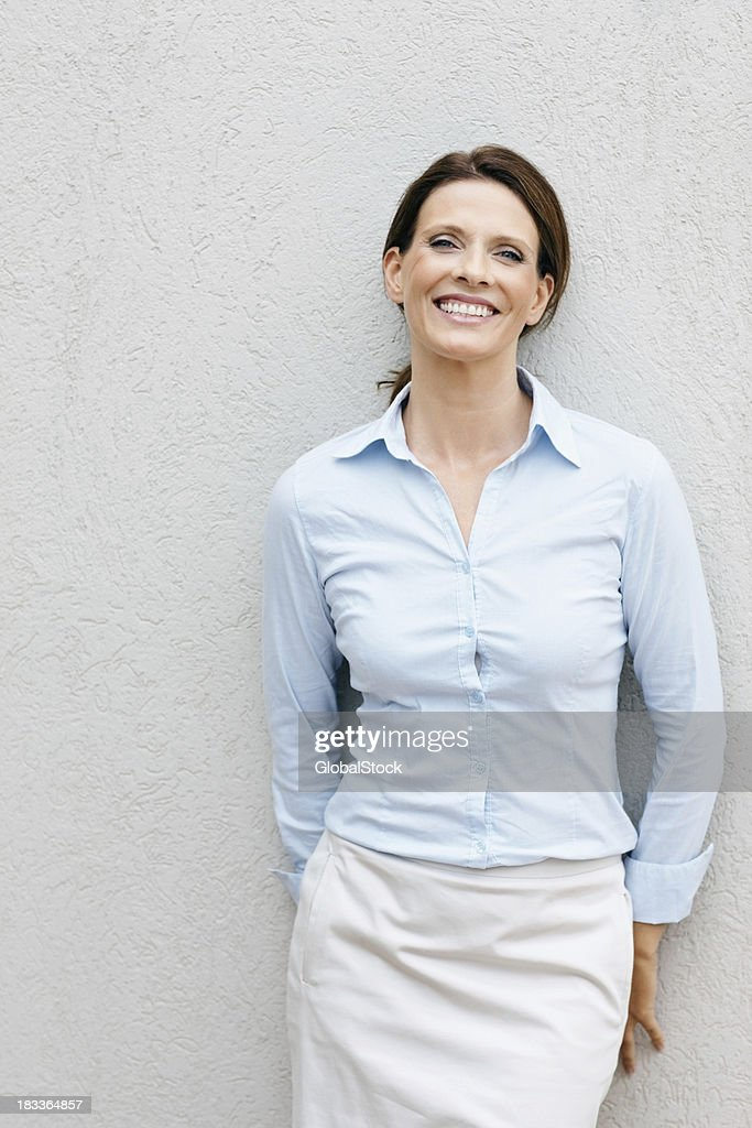 'Smiling, mature businesswoman leaning against a wall'