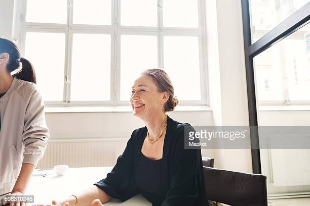 Smiling mature businesswoman with female colleague in conference room