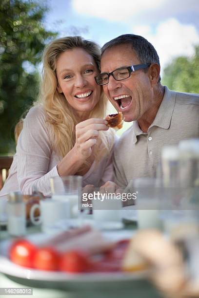 Smiling mature couple having breakfast outdoors