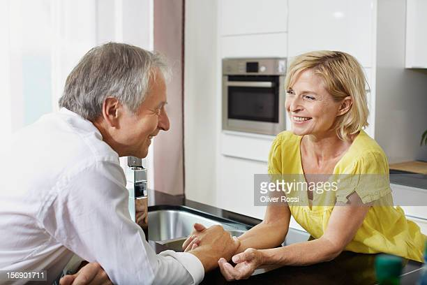 Smiling mature couple holding hands in kitchen