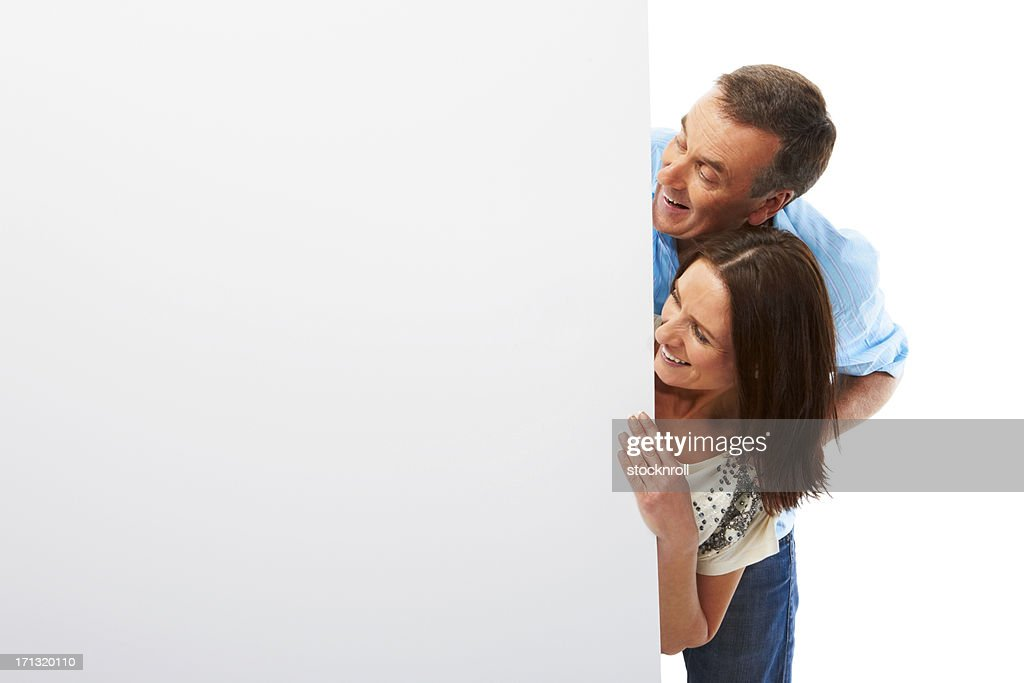 Smiling mature couple looking at empty billboard