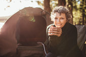 Portrait of a happy mature woman holding coffee cup while sitting in front of a tent and looking at camera. Senior caucasian woman having tea at campsite on a sunny day.