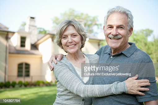 Smiling mature couple outside home : Stock Photo