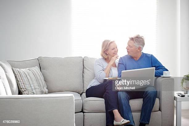 Sorridente Casal sentado em casa em discussão com computador portátil