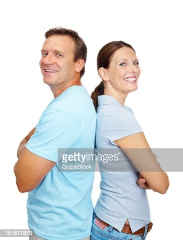 Smiling mature couple standing with arms crossed against white