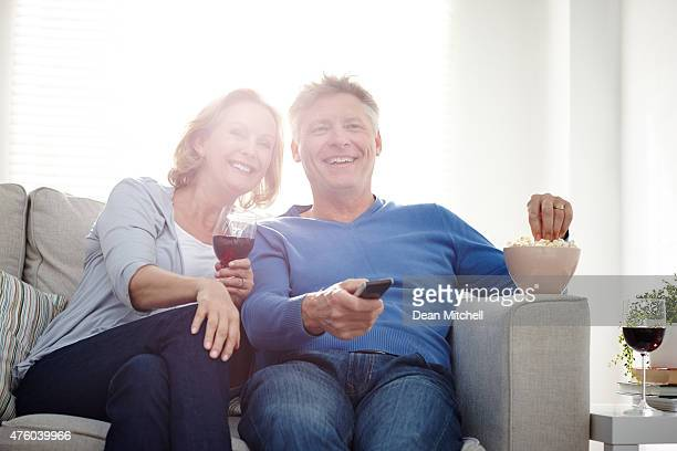 Smiling mature couple watching TV together