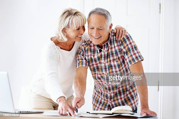 Smiling mature couple with book, map and laptop
