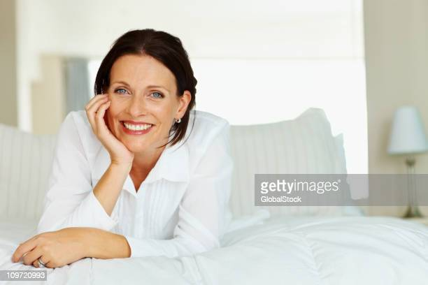 微笑む熟年女性のベッドに横たわる