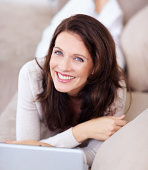 Smiling mature lady lying on couch and using laptop