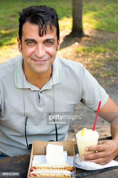 Lächelnde reifer Mann dem Mittagessen in einem park