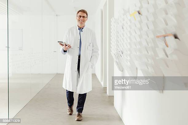 Smiling mature man in lab coat walking in hallway