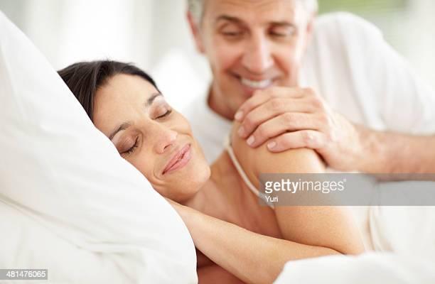 Uomo maturo sorridente guardando la moglie che dorme sul letto