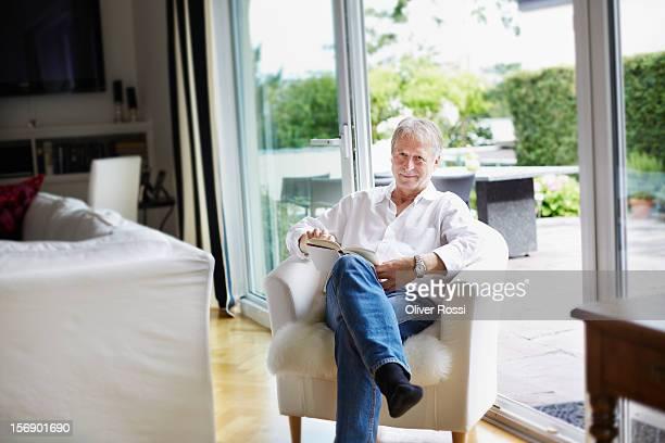 Smiling mature man reading book at home