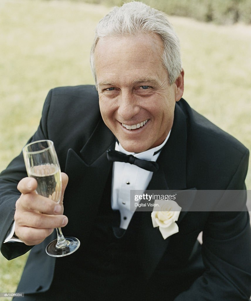 Smiling, Mature Man Sitting and Holding a Champagne Flute : Stock Photo