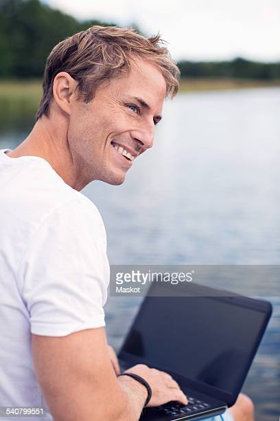 Smiling mature man using laptop while looking away at lake