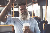Smiling mature man with a long beard drinking a takeaway cup of coffee while standing on a bus during his morning commute