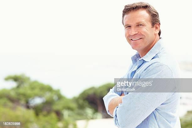 Lächelnd Reifer Mann mit Armen gekreuzt stehen im Freien