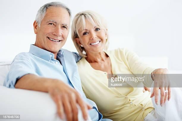 Lächelnd Reifer Mann mit seiner Frau sitzen zusammen auf Couch