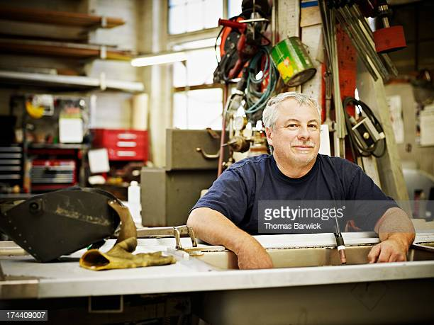 Smiling mature sheet metal worker sitting in shop