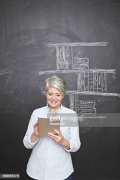 Smiling mature teacher standing at blackboard holding digital tablet