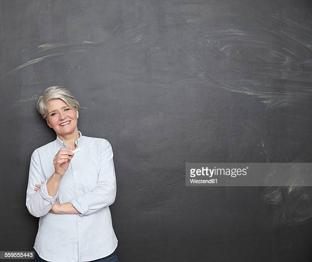 Smiling mature teacher standing at blackboard