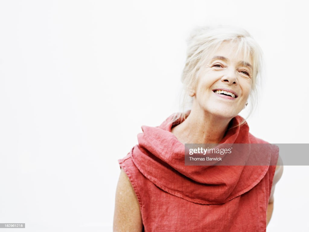 Smiling mature woman against white background : Stock Photo