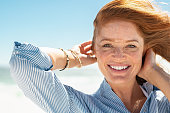 Portrait of beautiful mature woman with wind fluttering hair. Closeup face of healthy young woman with freckles relaxing at beach. Cheerful lady with red hair and blue blouse standing at seaside enjoy