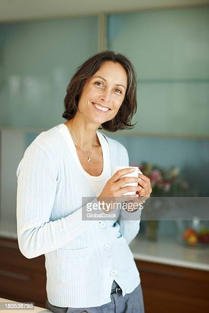 Smiling mature woman having a cup of coffee in kitchen