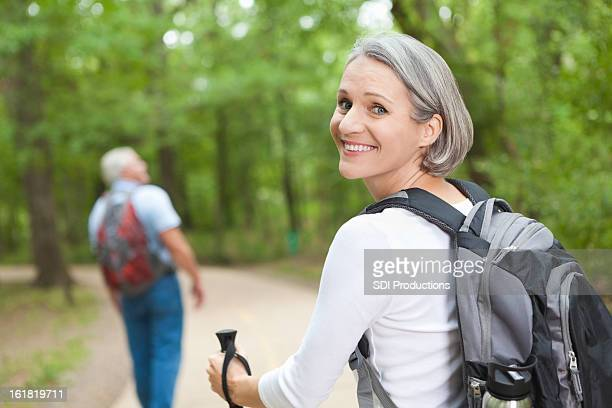 Smiling mature woman hiking on trail with husband