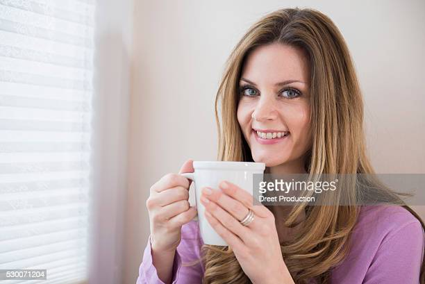 Smiling mature woman holding cup at the window