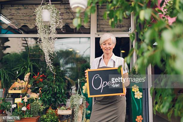 Smiling mature woman holding open sign at flower shop.