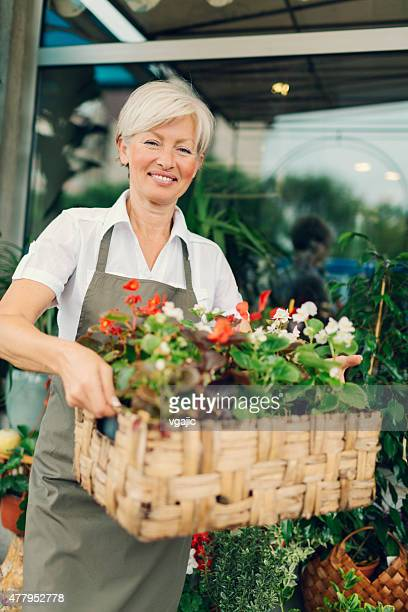 Smiling mature woman holding with flowers outside flower shop.
