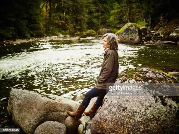Smiling mature woman leaning against rock