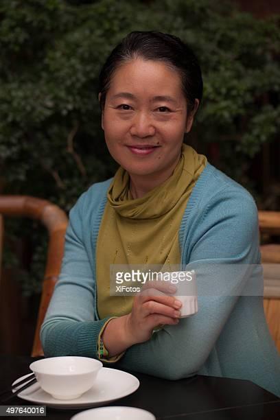 Souriant mature femme de l'Est asiatique tenant la tasse de thé