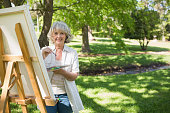 Portrait of a smiling mature woman painting on canvas in the park
