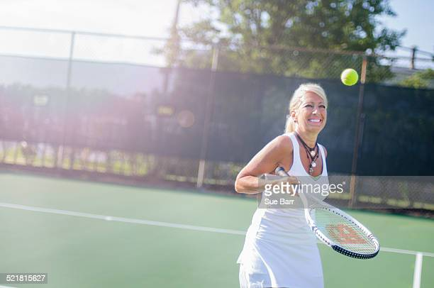 Smiling mature woman playing tennis