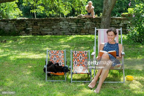 Smiling mature woman reading book in garden