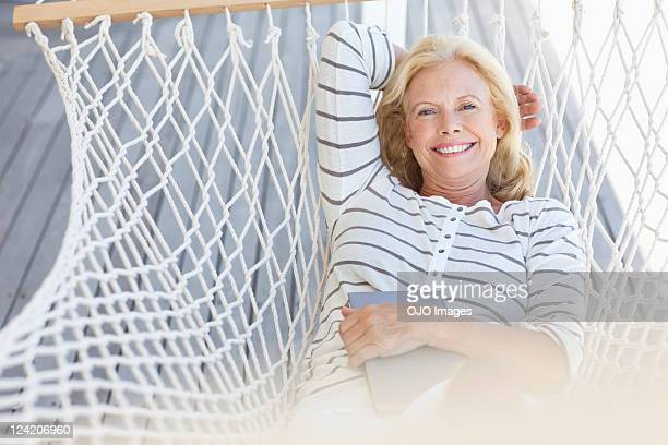 Smiling mature woman relaxing in hammock with a book