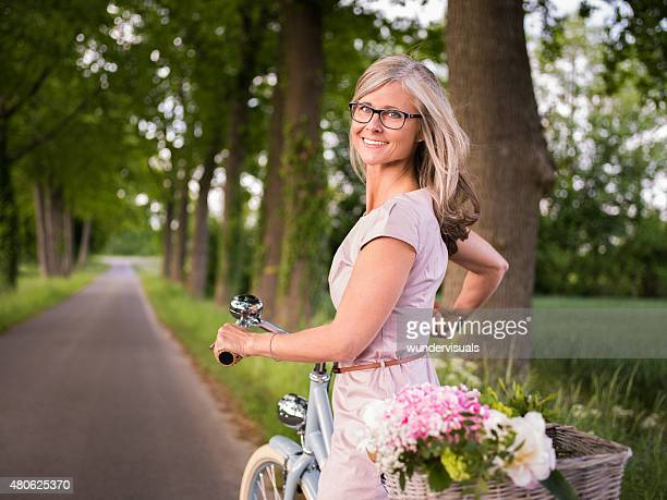 Smiling mature woman riding her bicycle in a park