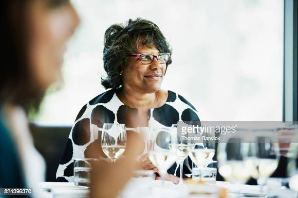 Smiling mature woman seated at head of table during family celebration meal in restaurant