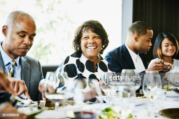 Smiling mature woman sharing a meal with family in restaurant